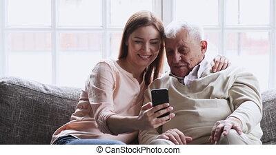 petite-fille, papy, rire, smartphone, utilisation, embrasser, gai, aîné