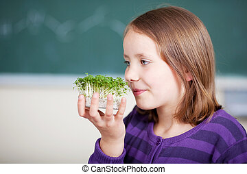 Petri dish - Female student holding and smelling the cress...