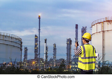 Petrochemical engineering man standing in oil refinery.