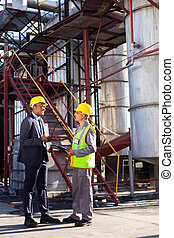petrochemical manager in discussion with plant worker -...