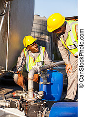 petrochemical wokers inspecting pressure valves on fuel tank...