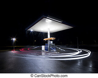 Petrol station at night with traffic in movement