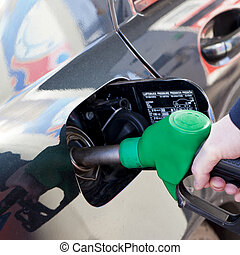 petrol tank - man filling up car with fuel at petrol station