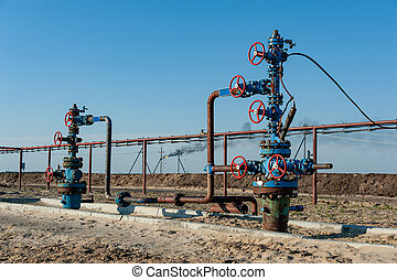 Petroleum well wellhead equipment. Hand valve with handwheel on the flow line. Oilfield site. Oil, gas industry concept. Industrial site background. Production oil. Multiple check valve gate armature.