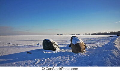 PETROZAVODSK, RUSSIA - JANUARY 21, 2014:  Onega lake embankment view with several granite stones and pedestrians passing by in winter day, slider.