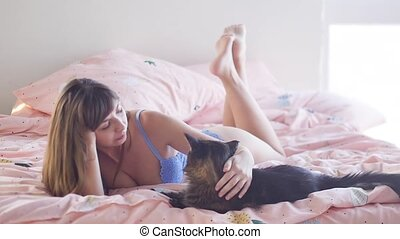 Pets and people. Beautiful young woman in lingerie with a big Maine Coon cat in bed at home