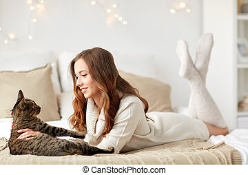 happy young woman with cat lying in bed at home - pets,...