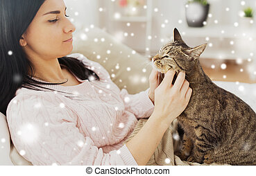 close up of woman with tabby cat in bed at home
