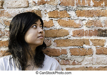Petty young brunette woman  against a Brick Wall
