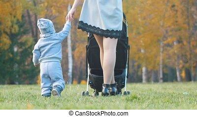 peu, elle, mère, voiture, marche, jeune, tenant mains, fils bébé