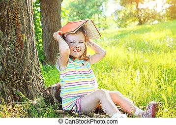 peu, fille souriante, enfant livre, jouer, herbe, dans, ensoleillé, jour été