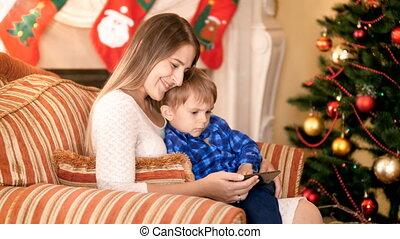 peu, hiver, elle, regarder, fauteuil, séance, arbre, fils, décoré, vidéo, fond, mère, sourire, fetes, cheminée, noël, smartphone., heureux
