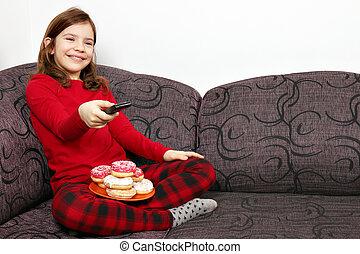 peu, manger, regardant télé, beignets, girl