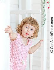 peu, mignon, girl, dans, a, robe rose, regarde, dans, les, rue, à, a, surpris, regard, par-derrière, les, blanc, porte, sur, les, porch., provence, style