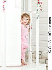 peu, mignon, girl, dans, a, robe rose, regarde, dans, les, rue, et, sourire, par-derrière, les, blanc, porte, sur, les, porch., provence, style