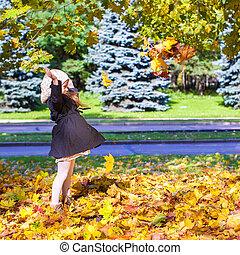 peu, rigolote, girl, jets, feuilles automne, dans parc, sur, a, ensoleillé, diminuez jour