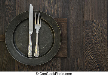 Pewter plate and vintage cutlery on rustic dark wooden background
