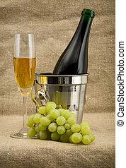 pezsgő palack, talpas pohár, szőlő, vödör