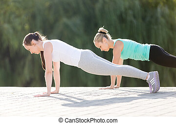 Phalankasana pose in pair - Group of two attractive sport...