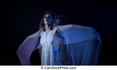 Phantom of young bride in white wedding dress and veil moving her hands. Poltergeist girl with halloween make-up is standing against black background. Mysterious woman in horror behind .