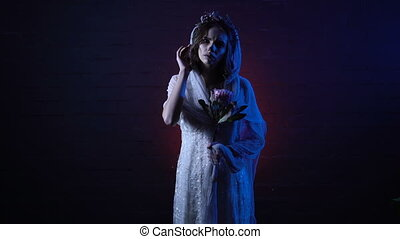 Phantom of young lonely dead bride standing with sad face and flower in her hand. Scary girl halloween apperance make-up is against horror background looking showing finger at the camera.