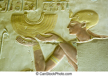 Ancient Egyptian bas relief carving showing the Pharaoh Seti I holding a gold collar style necklace. Abydos Temple, el Balyana, Egypt. Ancient carving on public display over 1000 years.