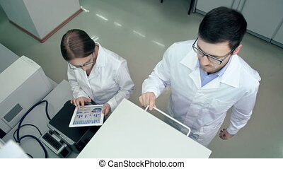 Above view of two lab colleagues testing pharmaceutical sample using centrifuge