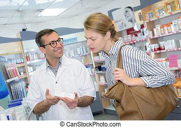 Pharmacist advising female customer