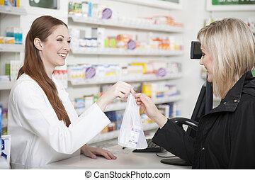 Pharmacist and customer in pharmacy - Friendly female ...