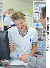 pharmacist assisting the box of medicine to customer in pharmacy