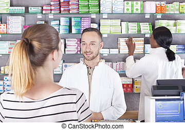 Pharmacist attending customer, showing product