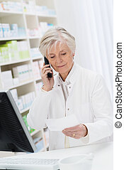Pharmacist checking a prescription over the phone