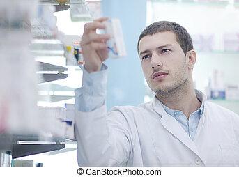 pharmacist chemist man in pharmacy drugstore