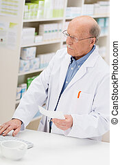 Pharmacist entering prescription details - Elderly male...