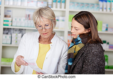 Pharmacist explaining the prescription to the female ...