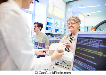 Pharmacist handing medication to customer