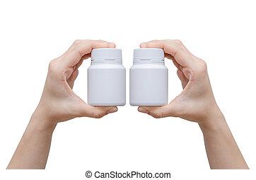 hands holding medicine bottles isolated on white
