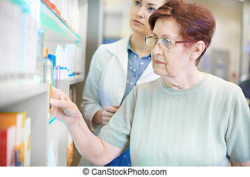 Pharmacist helping senior woman with prescription