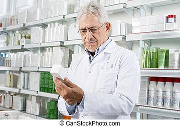 Pharmacist Holding Medicine Box In Pharmacy