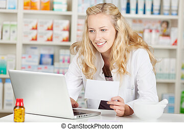 Pharmacist Holding Prescription While Using Laptop At Coun