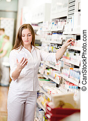Pharmacist Looking at Prescription - Attractive young...