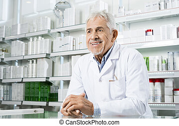 Pharmacist Looking Away While Leaning On Counter