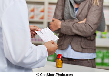 pharmacist reading prescription paper at the counter