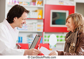 Pharmacist Receiving Prescription Paper From Customer