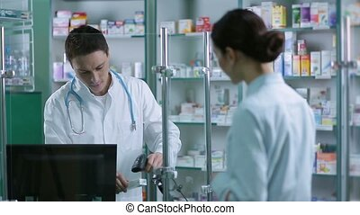Pharmacist scanning medicines with barcode reader -...