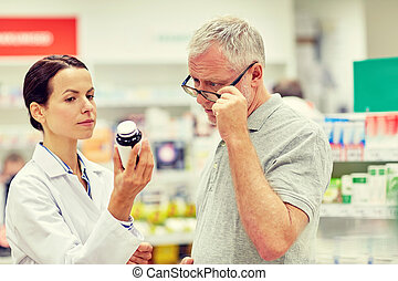 pharmacist showing drug to senior man at pharmacy