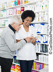 Pharmacist Showing Information On Product To Senior Customer