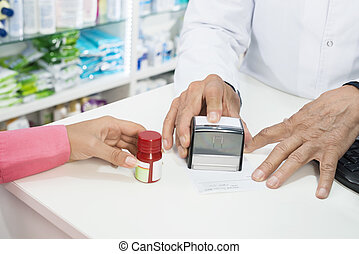Pharmacist Stamping Paper While Customer Holding Pill Bottle