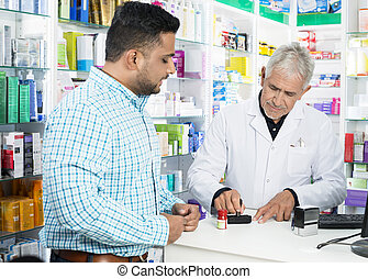 Pharmacist Stamping Paper While Customer Standing At Counter