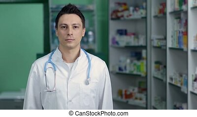 Pharmacist standing with crossed arms in pharmacy - Portrait...
